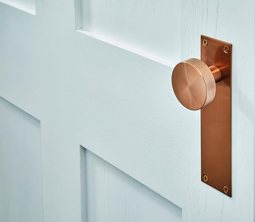 Copper flat plate door handle on whit door