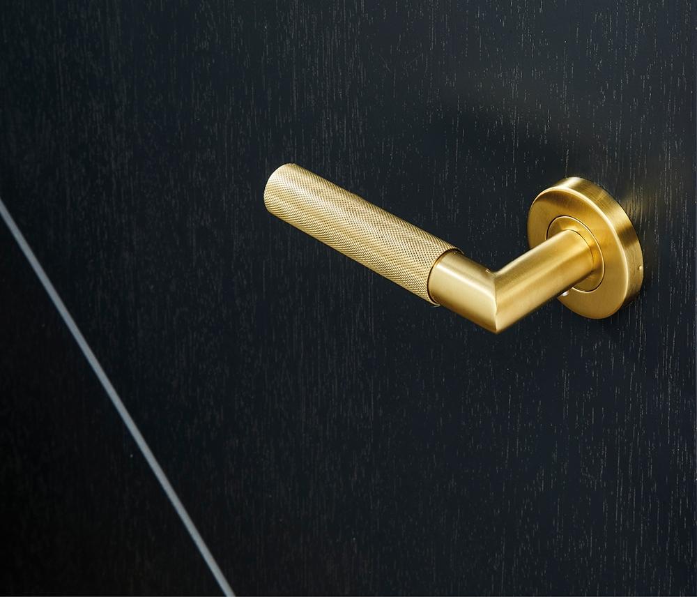 Gold door handle on black internal door