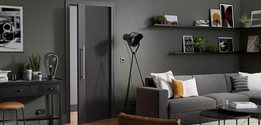 A black internal door with deep groves